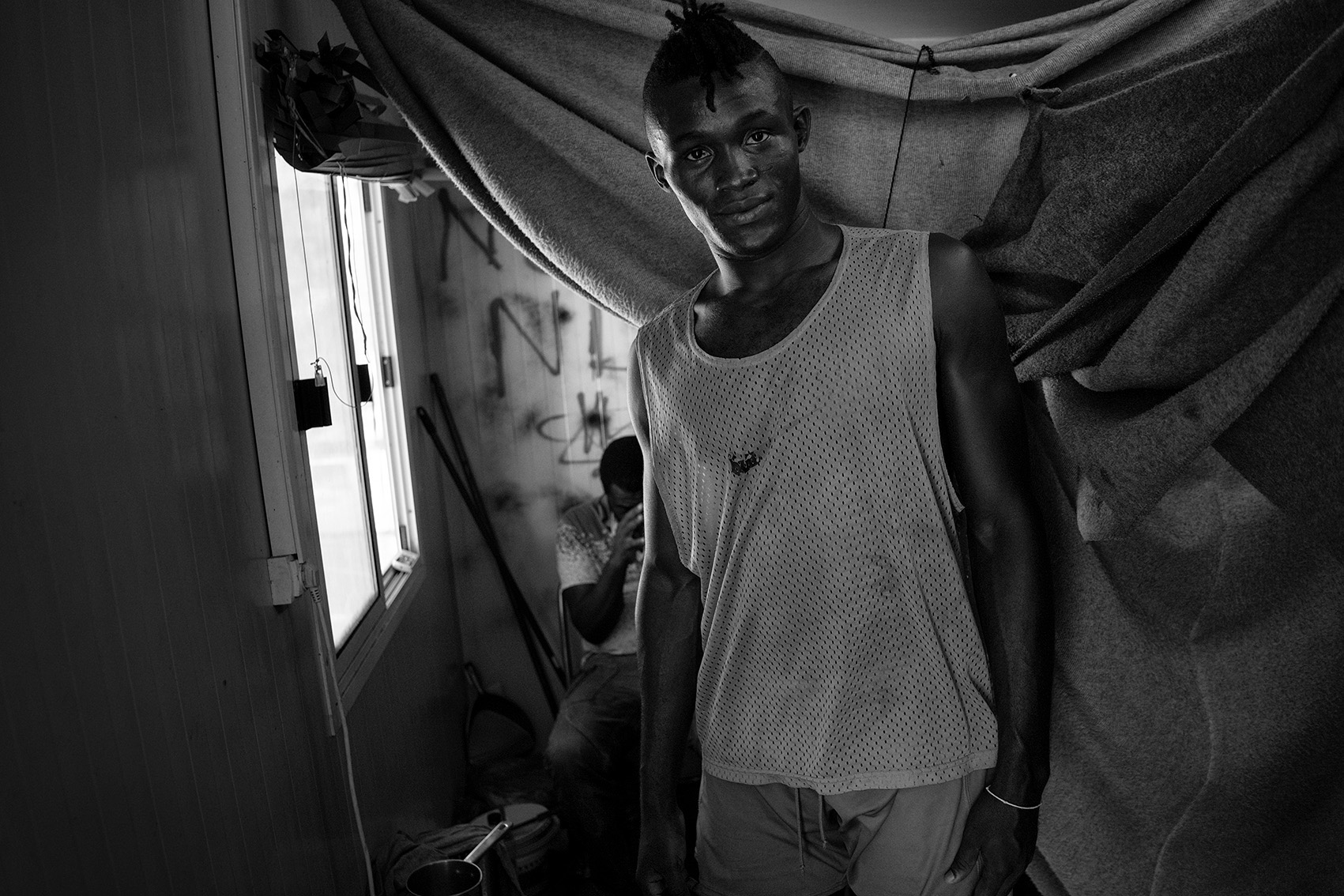 Ali, a professional football player from Guinee, inside his container at the refugee camp Moria. He lives together with 4 other refugees from Africa, their beds divided by blankets, Lesvos, Greece.