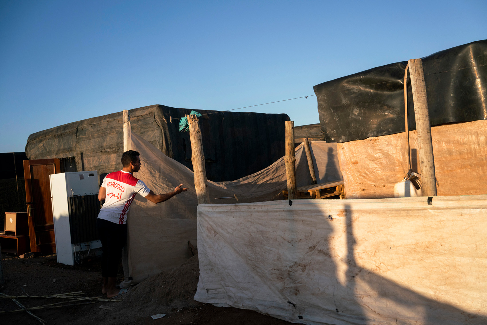 A Moroccan migrant worker living in a ghetto of self-constructed shovels made of plastic sheeting, Spain.